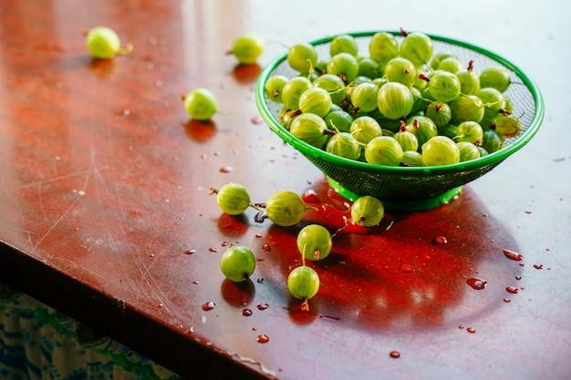 Hoop van groen nat gewassen kruisbessenfruit in een vergiet op lijst. een verspreiding van grote sappige bessen op de tafel