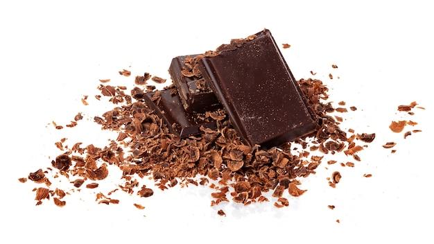 Hoop van grond en geraspte chocolade die op witte achtergrond wordt geïsoleerd