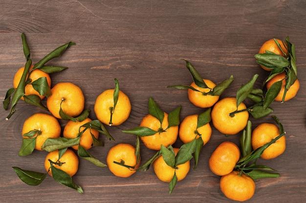 Hoop van mandarijnen met groene bladeren op rustiek hout