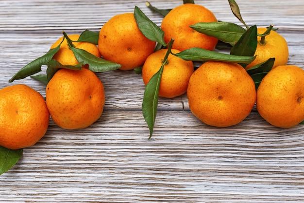 Hoop van mandarijnen met groene bladeren op rustieke houten achtergrond met exemplaarruimte.