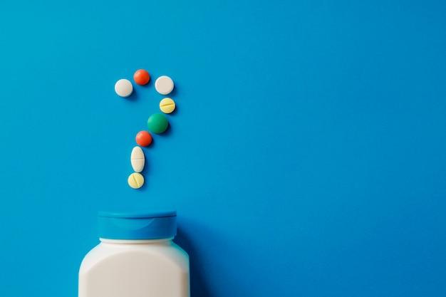 Hoop van pillen op blauw diverse farmaceutische geneeskundepillen, tabletten en capsules en fles op blauw