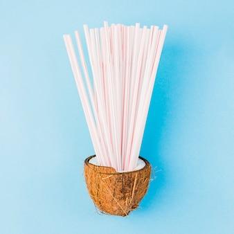 Hoop van plastic rietjes in kokosnoot