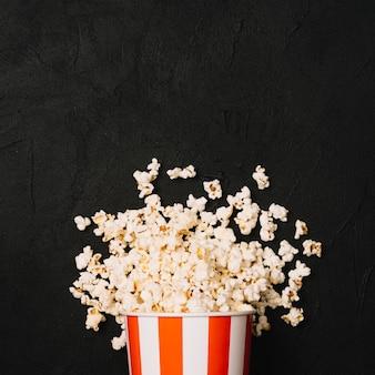 Hoop van popcorn die van gestreepte emmer wordt gemorst