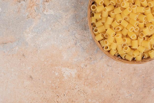 Hoop van ruwe ditalini-deegwaren op houten mand.