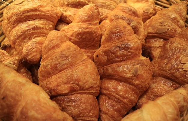 Hoop van vers gebakken overheerlijke amandelcroissantgebakjes in de bakkerijwinkel