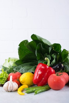 Hoop van verse groenten en fruit op houten achtergrond. paksoi peper kool greens artisjok courgette komkommer tomaat knoflook