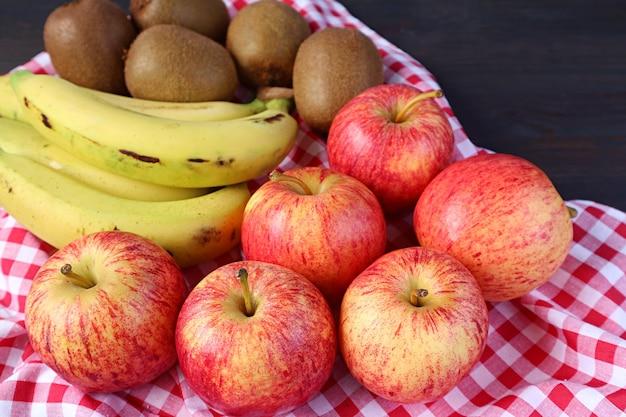 Hoop van verse rijpe appels, bananen en kiwi's op geruite doek voor het concept van goed eten