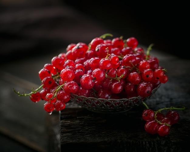 Hoop van verse rode bessen met waterdruppels in een metalen kom op oude donkere houten achtergrond