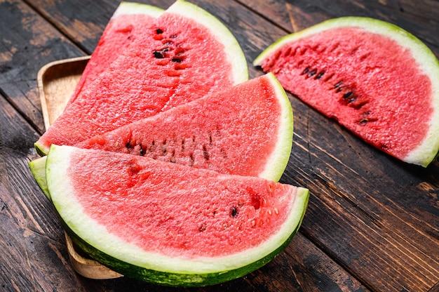 Hoop van verse rode gesneden watermeloen. donkere houten achtergrond. bovenaanzicht.