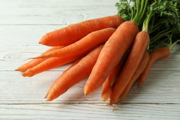 Hoop van verse wortel op witte houten tafel