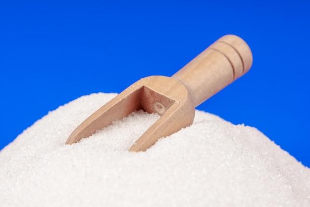 Hoop van witte suiker met een houten lepel op een blauwe achtergrond