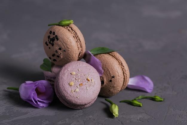 Hoop van zoete franse macarons gemengd met bloemen op een grijze betonnen ondergrond. pastelkleurige bitterkoekjeskoekjes. voedsel-, culinair-, bakkerij- en kookconcept