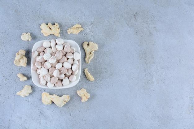 Hoop van zoete ronde snoepjes op een stenen oppervlak
