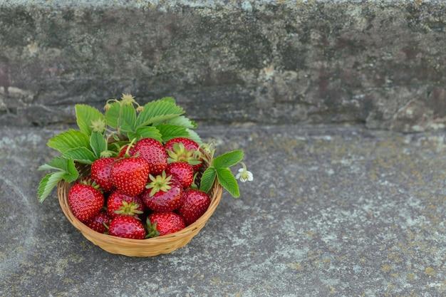 Hoop verse aardbeien in een mandkom op betonnen ondergrond