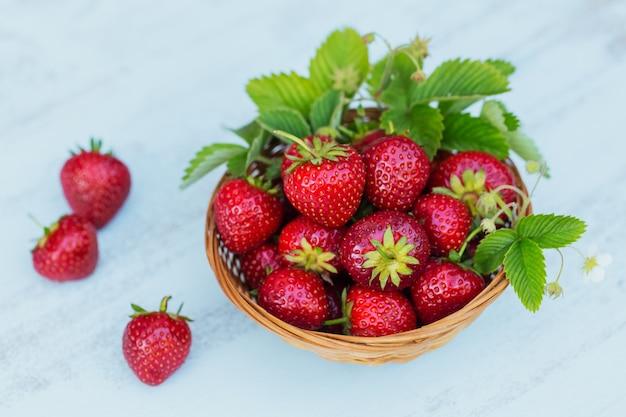 Hoop verse aardbeien in een mandkom op lichte houten achtergrond. gezond eten en dieet food concept.