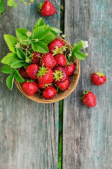 Hoop verse aardbeien in een mandkom op rustieke houten achtergrond