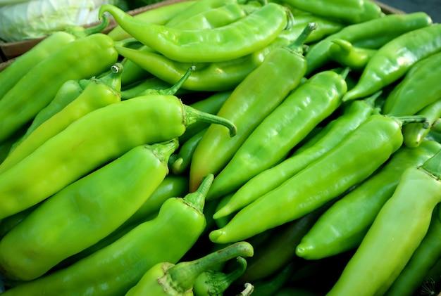 Hoop verse groene chilipepers te koop op de markt