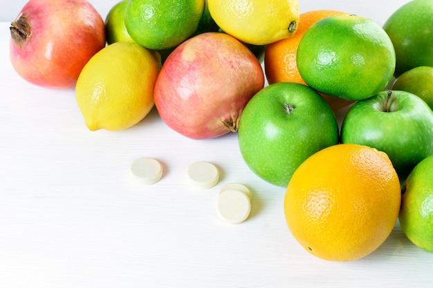 Hoop verse verschillende citrusvruchten (groene appels, mandarijnen, sinaasappels, granaat, citroen) en multivitaminen