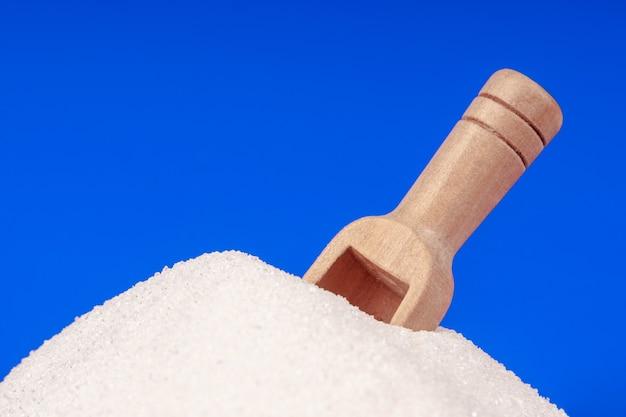 Hoop witte suiker met een houten lepel