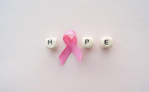 Hoop woord met roze lint op de helder roze achtergrond, de voorlichting van borstkanker en de voorlichting van de buikkanker. werelddag voor kanker