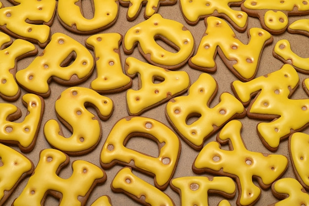 Hoop zelfgemaakte gele letters gemaakt van peperkoek biscuit achtergrond.