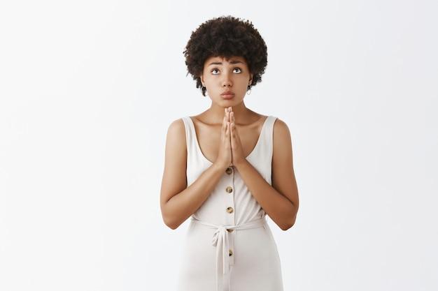 Hoopvol en bedelend stijlvol meisje poseren tegen de witte muur