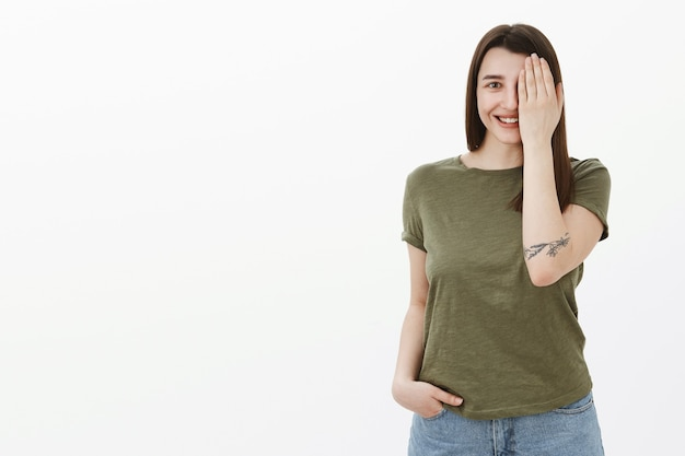 Hoopvol en opgewonden jonge schattige europese brunette in de jaren 20 met tatoeage-omslagoog en de helft van het gezicht als breed glimlachend gluren verrukt