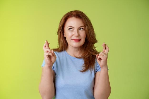 Hoopvol enthousiaste gember roodharige van middelbare leeftijd vrouw bidden geloven droom die uitkomt in afwachting van wonder anticiperen op goede positieve resultaten bijten lip verleiding opzij kijken doen wensen kruis vingers geluk
