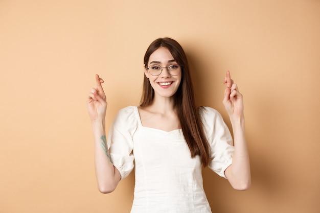 Hoopvol lachend meisje dat wens doet, vingers voor geluk kruist en er gelukkig uitziet, bidt dat de droom uitkomt, staande op een beige achtergrond.