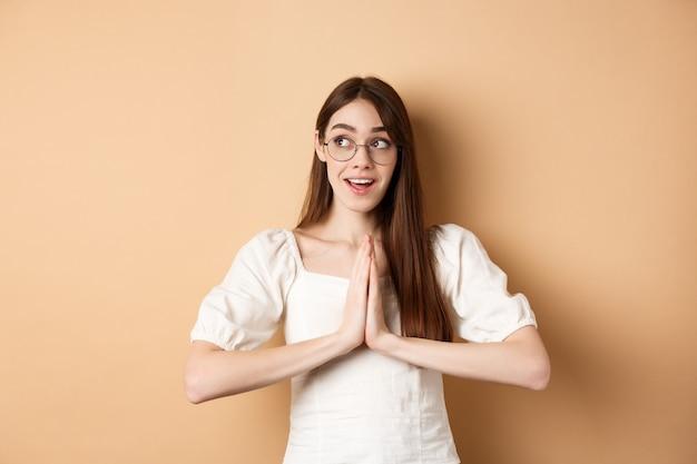 Hoopvol meisje hand in hand in gebed, smekend om droom die uitkomt, opgewonden opzij kijken, staande op beige achtergrond. kopieer ruimte