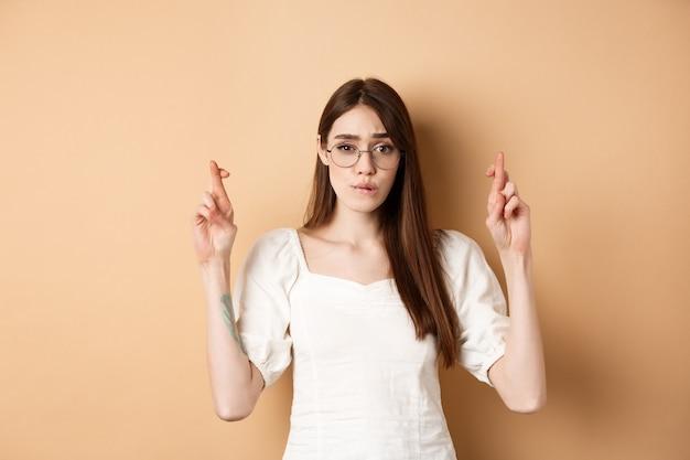 Hoopvol meisje met een bril kruist de vingers voor veel geluk, ze bijt nerveus op de lip en kijkt naar de camera die wacht...