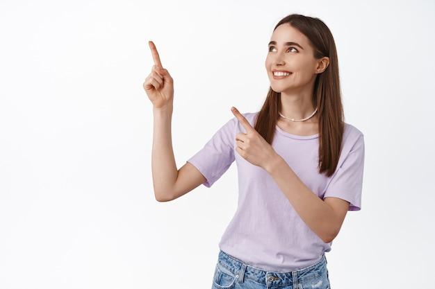 Hoopvol mooi meisje wijzend, kijkend naar de linkerbovenhoek met een blij lachend gezicht met item te koop op wit.