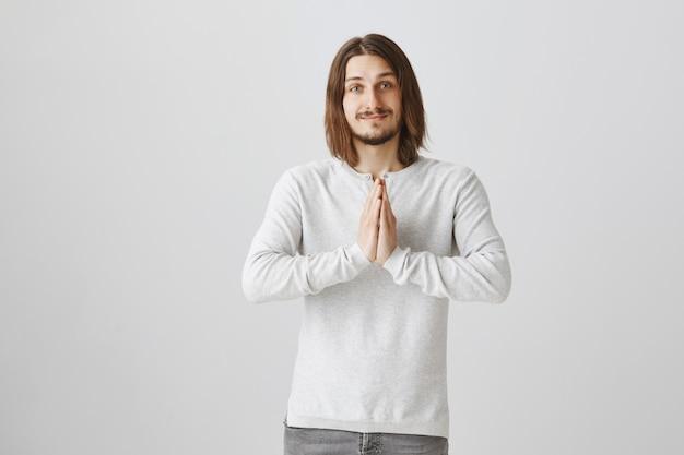 Hoopvol pleitende jonge man lacht, hand in hand in bid