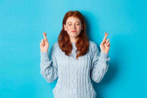 Hoopvol roodharig meisje dat een wens doet, vingers kruist voor geluk, glimlacht en anticipeert op goed nieuws of positief resultaat, staande tegen een blauwe achtergrond.