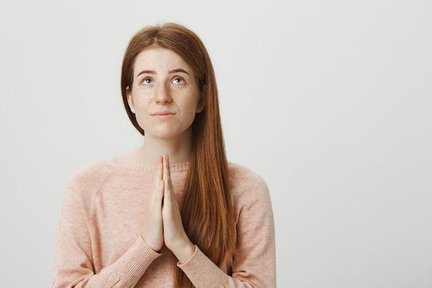 Hoopvol roodharig meisje smeekt god, houdt handen vast in een gebed en kijkt omhoog