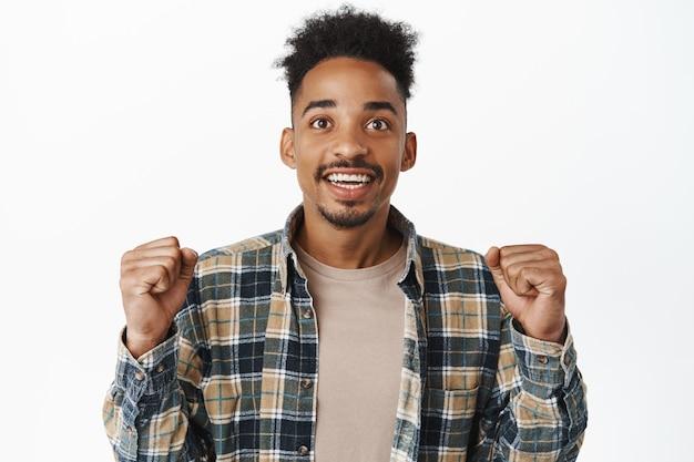 Hoopvolle afro-amerikaanse man die opgewonden kijkt, gebalde vuisten opgewonden, omhoog kijkt naar het tv-scherm, spel kijkt, wroet voor team, anticipeert op resultaten, wedden op wit.