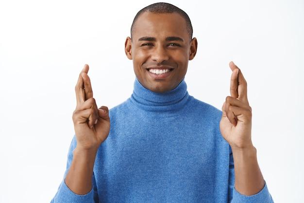 Hoopvolle afro-amerikaanse volwassen man die vertrouwen heeft in een droom die uitkomt, anticiperend op de vervulling van de wens, kruis vingers veel geluk