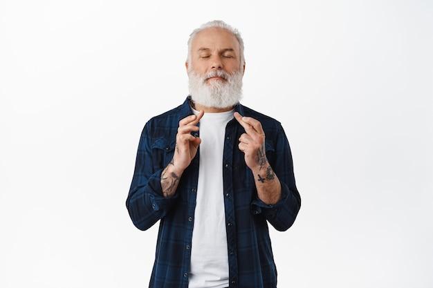 Hoopvolle bebaarde senior man kruist vingers, doet wensen, hopen of bidden voor iets, sluit de ogen en gelooft in dromen die uitkomen, staande over een witte muur