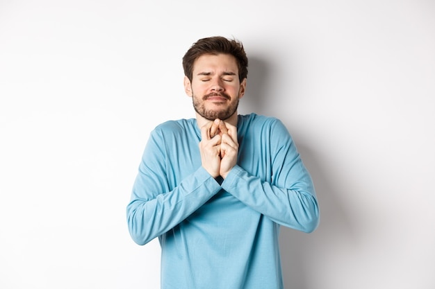 Hoopvolle blanke man in sweatshirt kruist vingers voor geluk. jonge man die wens doet, bidt met gesloten ogen en dromerige glimlach, staande op een witte achtergrond