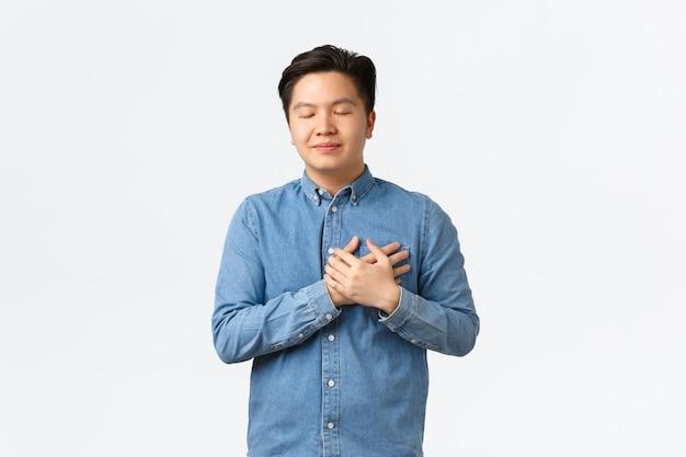 Hoopvolle dromerige aziatische man in shirt, ogen sluiten en handen op het hart houden, iets in beeld brengen, liefde en zorg voelen, mooie herinnering onthouden, aan iemand denken, witte achtergrond