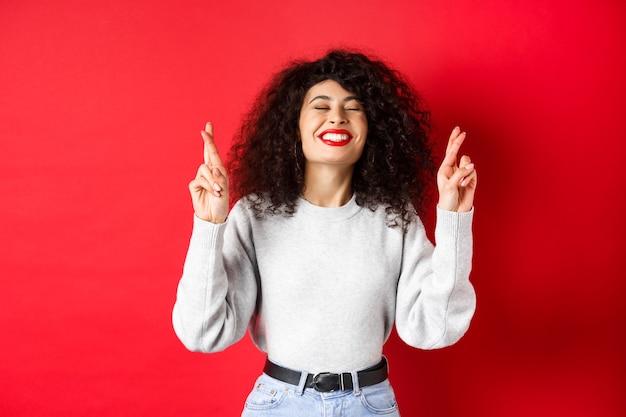 Hoopvolle en positieve vrouw met rode lippen en krullend haar, vingers gekruist voor geluk en wensen, biddend voor het uitkomen van een droom, opgewonden lachend, rode achtergrond.