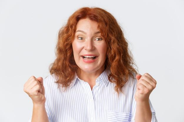 Hoopvolle gelukkige roodharige vrouw van middelbare leeftijd die op goed nieuws wacht