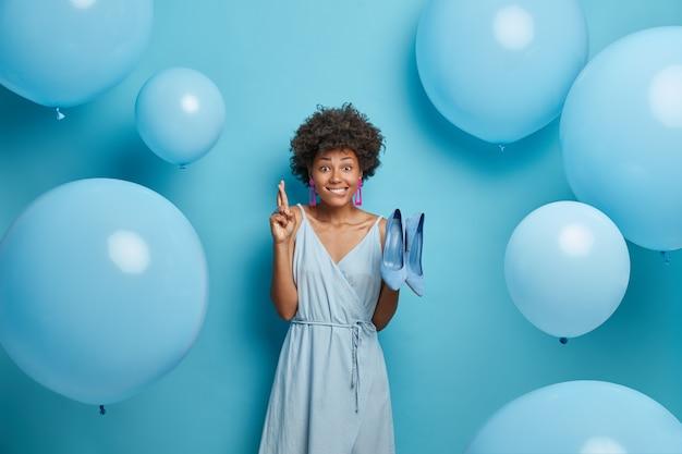 Hoopvolle jonge afro-amerikaanse vrouw kruist vingers, doet wensen, draagt schoenen en kleding met hoge hakken, jurken voor feest, staat binnen