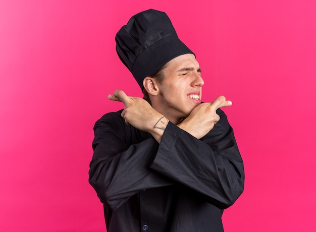 Hoopvolle jonge blonde mannelijke kok in chef-kokuniform en pet die de handen gekruist houdt en een geluksgebaar maakt met gesloten ogen