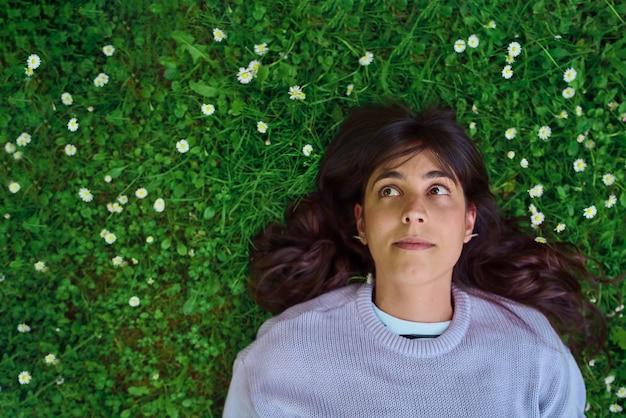 Hoopvolle jonge vrouw die opkijkt terwijl ze op het gras ligt, omringd door kleine madeliefjes bovenaanzicht