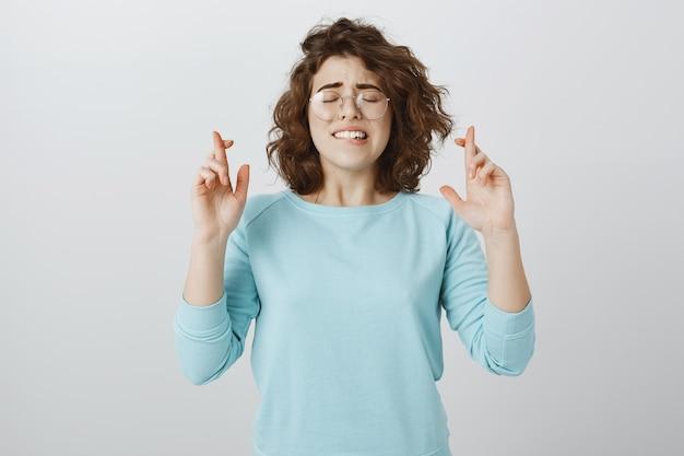 Hoopvolle jonge vrouw die wens doet, duimen voor geluk