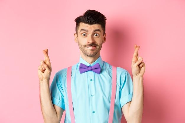 Hoopvolle jongeman die wens doet, vingers gekruist en glimlachend, wachtend op resultaten met optimisme, staande over roze achtergrond.
