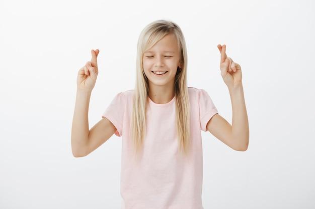 Hoopvolle kleine blonde vrouw die wens, kruis vingers veel geluk en lachend maakt