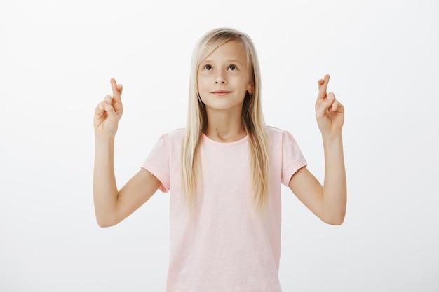 Hoopvolle kleine vrouw die een wens doet en in de lucht kijkt, kruis de vingers veel geluk
