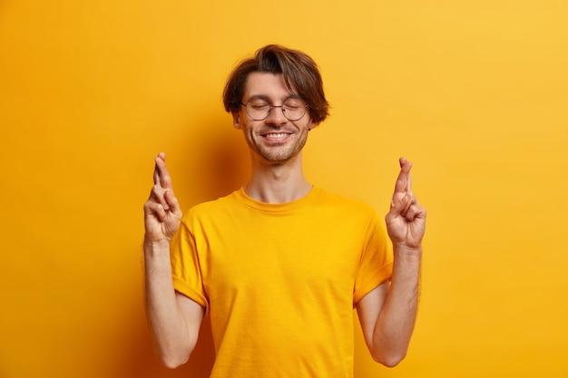 Hoopvolle lachende man met borstelige glimlach en houdt de vingers gekruist wacht op resultaten maakt wis hoop dromen uitkomen draagt ronde bril t-shirt geïsoleerd over gele muur. monochroom